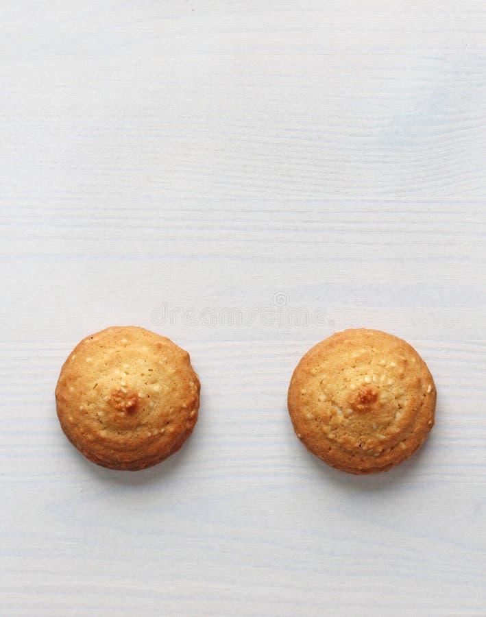Kakor på en vit bakgrund som är liknande till kvinnliga nipplar Sexiga nipplar i form av kakor Blidka den dubbla betydelsen arkivfoto