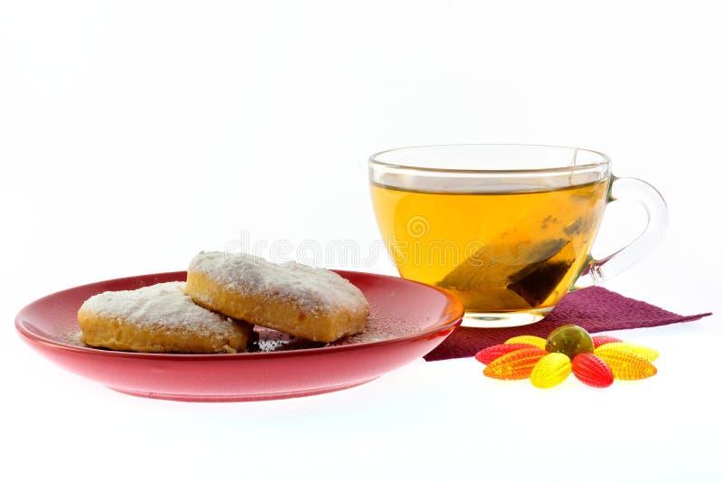 Kakor på ett röd tefat och kopp av svart te royaltyfri fotografi