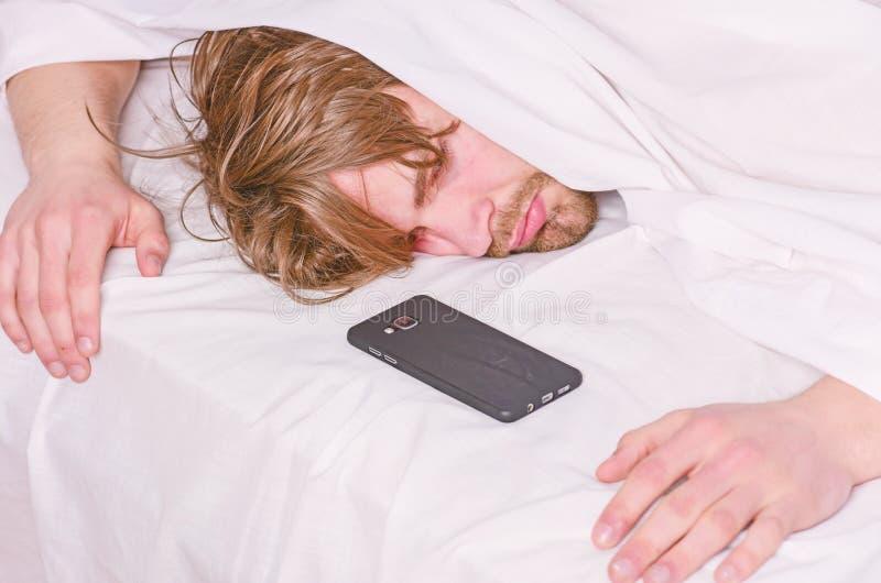 Kal fot av en man som ut fr?n under kikar lilla viken Den gladlynta unga mannen vaknar upp, n?r han har sovit i morgonen royaltyfri foto