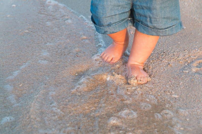 Kal fot som går på den sandiga stranden nära havet Behandla som ett barn lite i jeanskortslutningar som går att trycka på havet p arkivbilder
