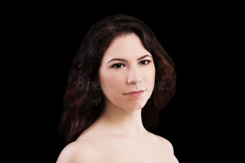 Kal skuldrastående av mörk bakgrund för ung Caucasian kvinna fotografering för bildbyråer