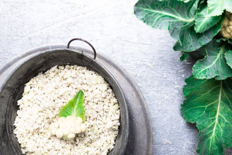 Kalafiorowi ryż w metalu rzucają kulą na popielatym tle Odgórny widok overhead kosmos kopii tarty fotografia royalty free