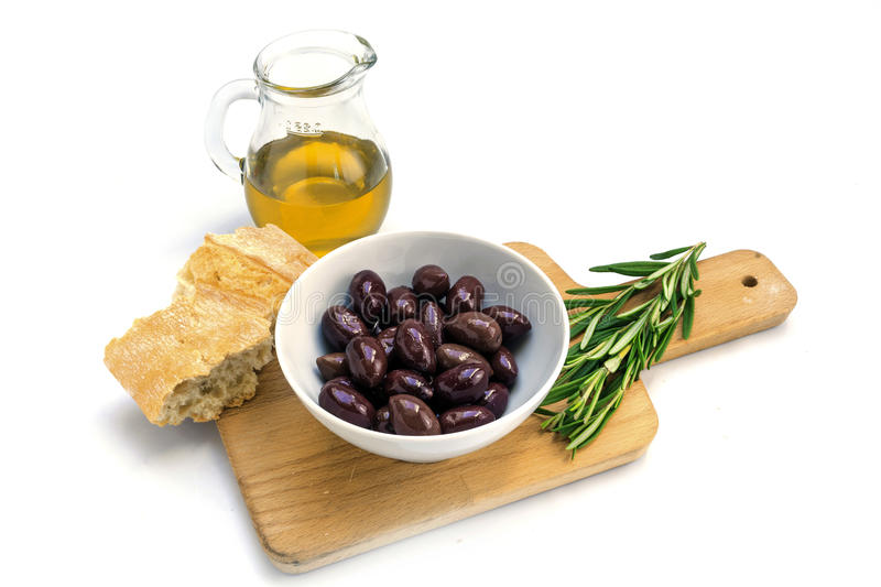 Kalamata black olives, olive oil, bread and rosemary garnish on. Kalamata black olives in a white bowl, olive oil, bread and rosemary garnish on a kitchen board stock photo