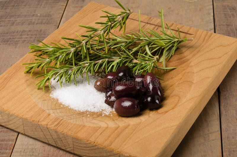 Kalamata oliv och rosmarinar som är förberedda arkivfoto