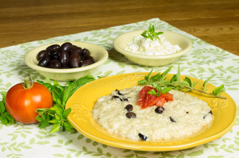 Kalamata olive risotto with tomatoes and herbs stock image