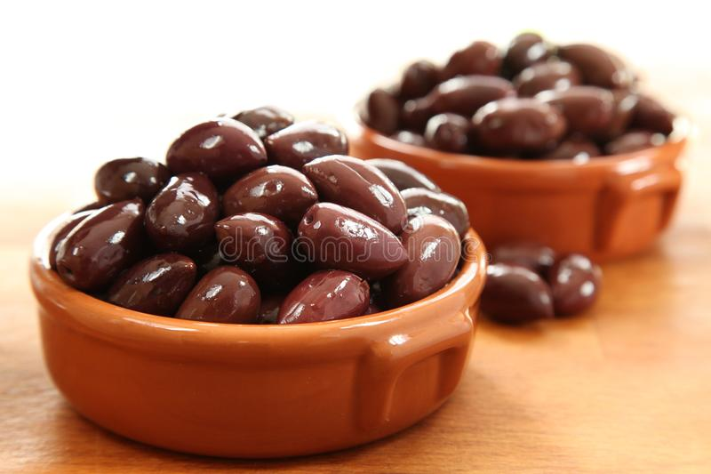 Kalamata Olives. In bowls on a wooden board royalty free stock photo