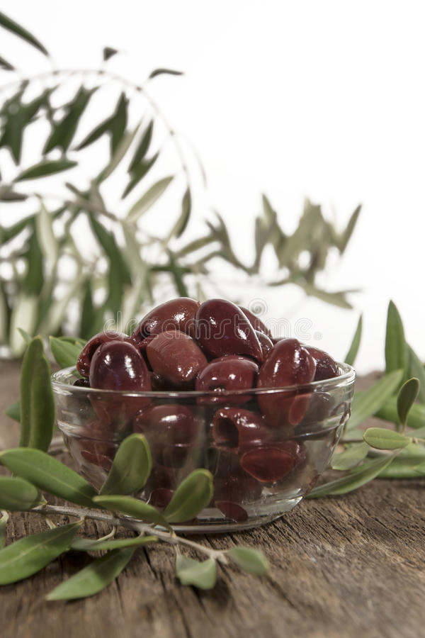Kalamata Olives Leaves. A glass bowl filled with Kalamata olives on rustic wood surface with olive branches. The Kalamata olive is a large, black olive with a royalty free stock photos