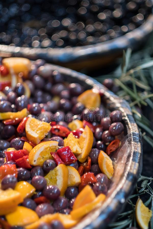 Kalamata olives marinated on market. Red kalamata olives marinated in oil decorated with oranges and peppers on display at market royalty free stock photography