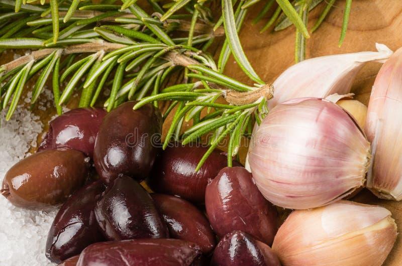 Kalamata olives and rosemary being prepared stock photo