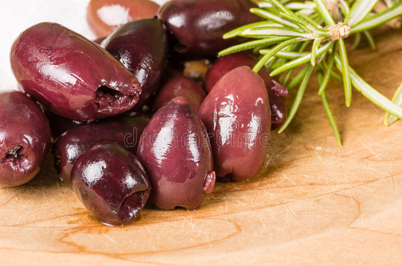 Kalamata olives and rosemary being prepared royalty free stock photography