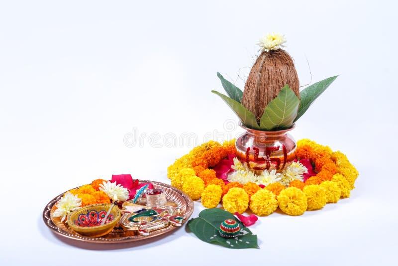 Kalash de cobre con el coco, la hoja y la decoración floral en un fondo blanco esencial en puja hindú foto de archivo