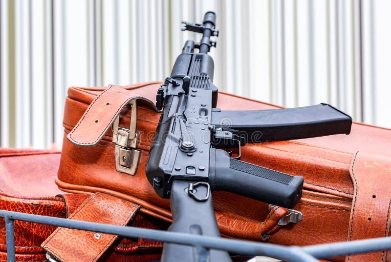 Kalashnikov ak-47 en uitstekende reiskoffers stock foto's