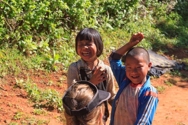 Kalaw högländer, Myanmar, November 18 2019 - lokala ungar i en liten by som spelar med en turist royaltyfria bilder