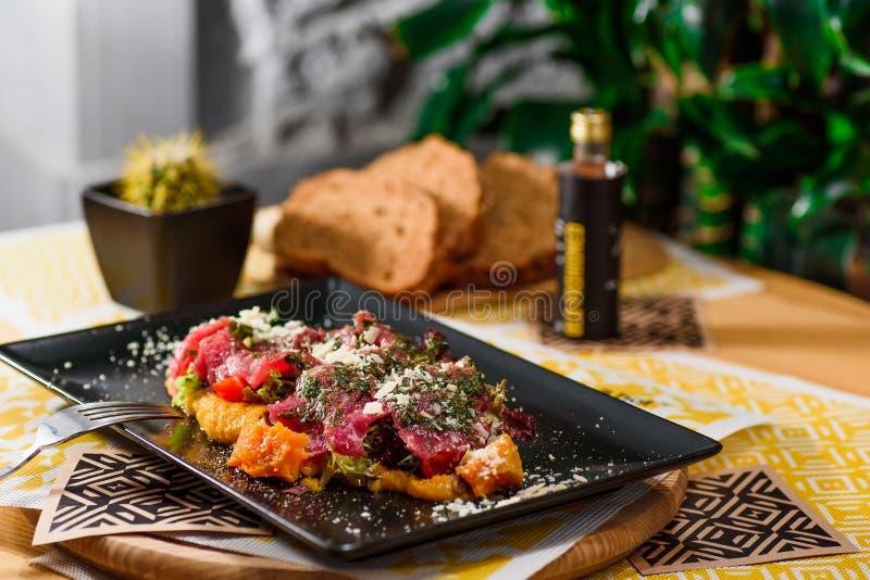 Kalbfleisch tartare auf Kürbispüree mit Parmesankäse, Kopfsalat und Tomaten, auf einem Schwarzblech stockfoto