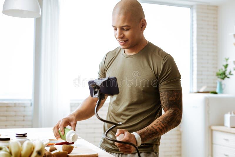 Kale bodybuilder die vitaminen nemen terwijl het koken van ontbijt stock fotografie