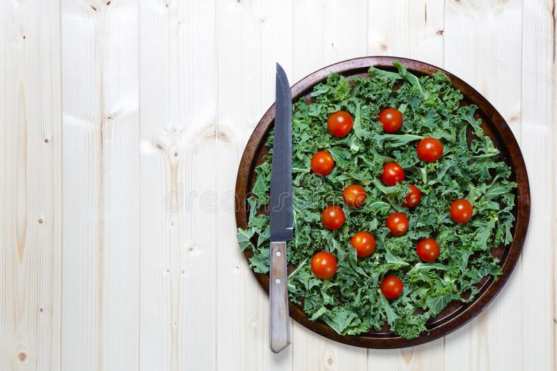 Kale with cherry tomatoes on metal tray with knife royalty free stock photography