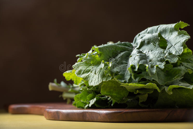 Kale on Cutting Board. Bunch of kale on cutting board with a yellow surface and dark background stock photo