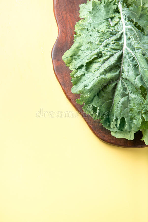 Kale on Cutting Board. Bunch of kale on cutting board with a yellow surface and dark background stock image
