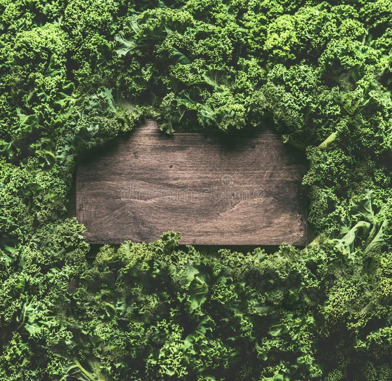 Kale leaves background frame with wooden sign. Healthy detox vegetables . Clean eating and dieting concept. Top view with copy. Space. Kale recipes and benefits stock photo