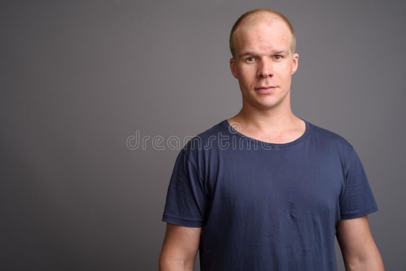 Kale mens die blauw overhemd dragen tegen grijze achtergrond stock foto