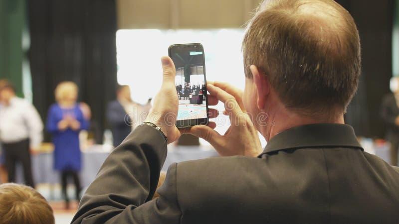 Kale mens die een smartphonetoekenning schieten bij de toernooien stock foto