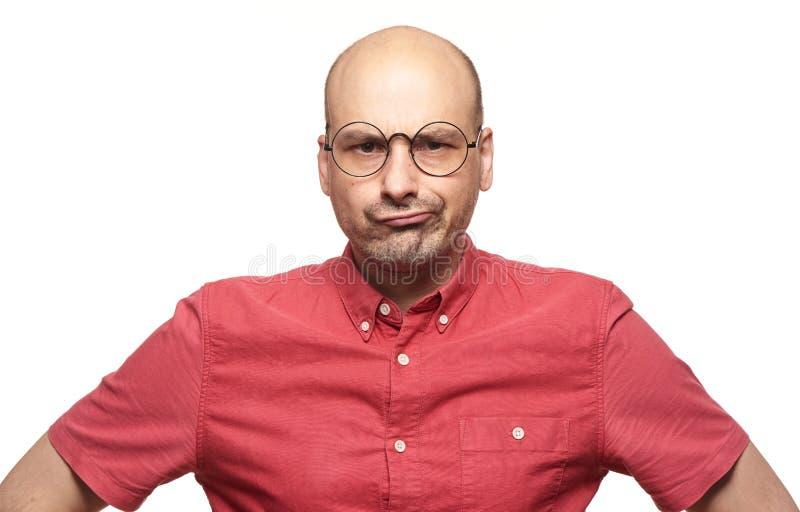 Kale mens met sceptische uitdrukking van zijn gezicht stock foto's