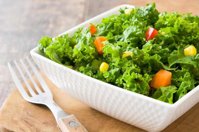 Kale salad in bowl with carrot, pepper and sweet corn stock image