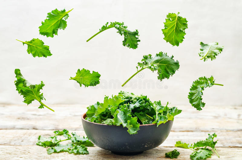 Kale salad with flying slices. On a wood background. tinting. selective focus stock images