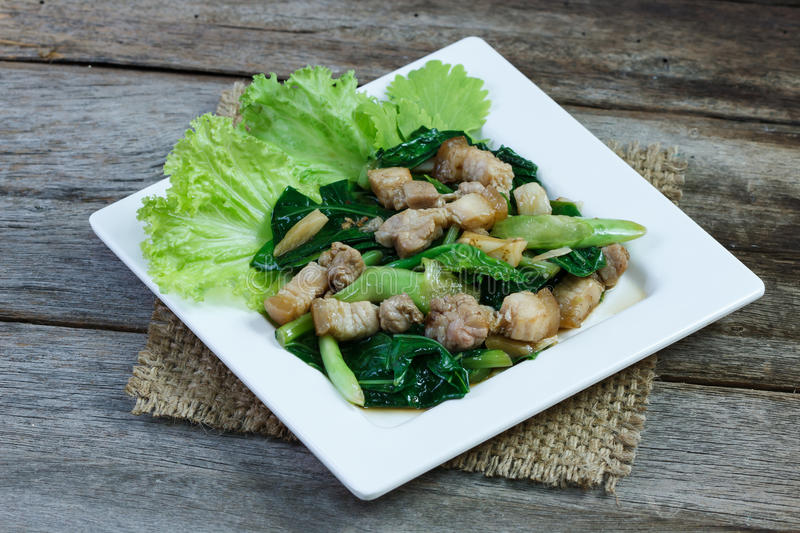 Kale and side pork fried in oyster sauce on white plate stock image