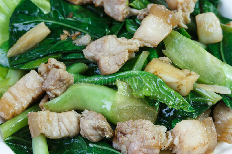 Kale and side pork fried in oyster sauce on white plate royalty free stock images