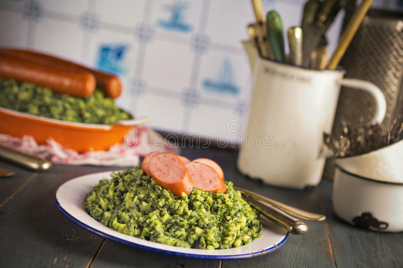 Kale with smoked sausage or 'Boerenkool met worst'. A rustic kitchen with a plate with 'Boerenkool met worst' or kale with smoked sausage, a traditional Dutch royalty free stock photos