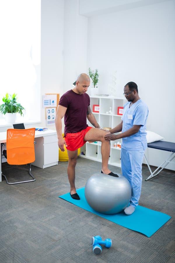 Kale sportman die zijn been op geschikte bal zet terwijl het bezoeken van therapeut stock foto's