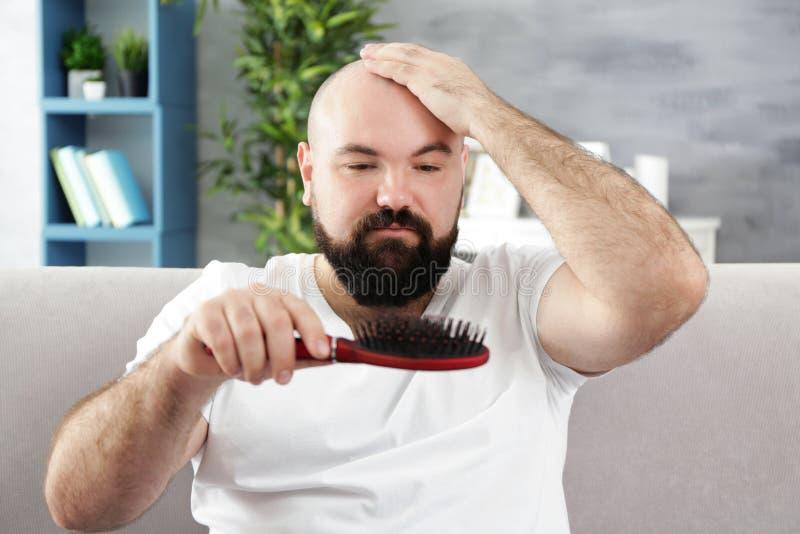 Kale volwassen mens met haarborstel stock afbeelding