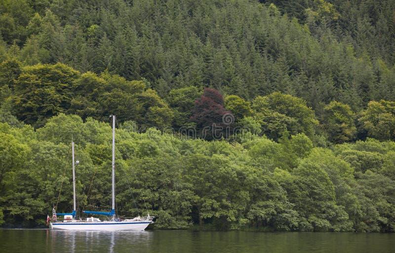 Kaledonischer Kanal mit Segelboot und Wald in Schottland stockfotografie