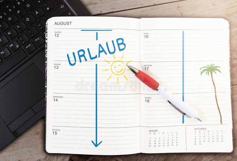 Kalender auf Tabelle mit dem Wort URLAUB, deutsch für Ferien und Sonnenikone gegen Holztisch lizenzfreies stockbild