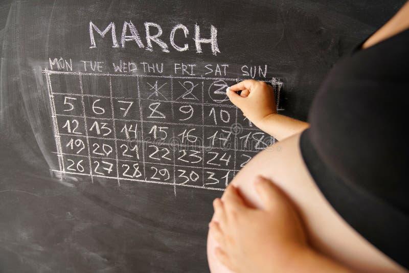 Kalender av gravida kvinnan månadmars som räknar dagar med en kalender för födelsen av ett barn på en svart tavla mot som kroken  fotografering för bildbyråer