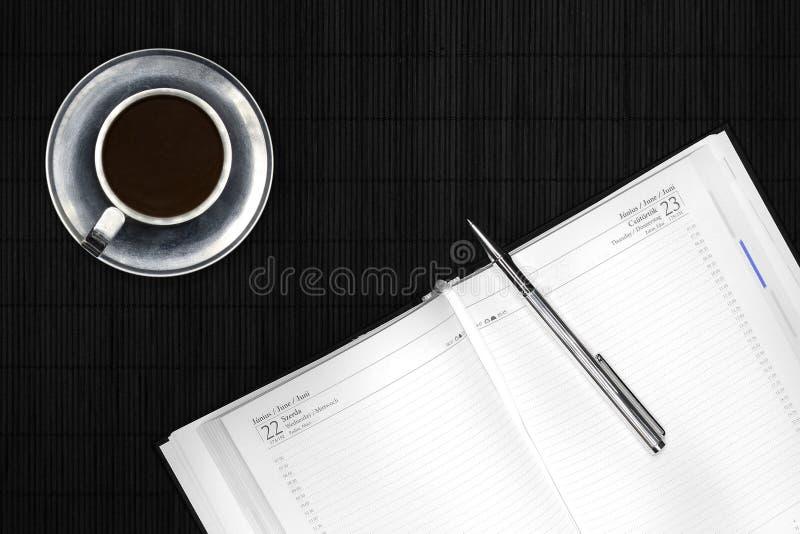 Kalender en zilveren pen op zwart bureau stock afbeeldingen