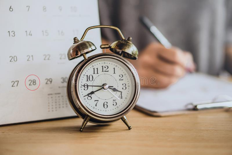 Kalender för förfallet datum med ringklockan på kontorsskrivbordet och suddighetsaffärskvinnan som arbetar i bakgrund arkivfoto