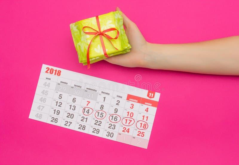 Kalender met duidelijke dagen van menstruatie in een meisje, vrouwelijke hand met een stapel sanitaire stootkussens, roze achterg stock afbeeldingen