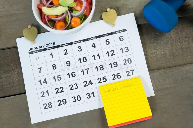 Kalender met nieuw van het jaarresolutie en dieet voedsel stock foto