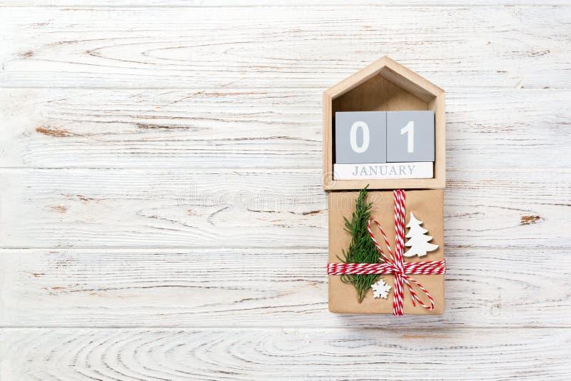 Kalender mit Datum am 1. Januar und Geschenkboxen auf Farbhintergrund Weihnachtsniederlassung und -glocken stockbilder