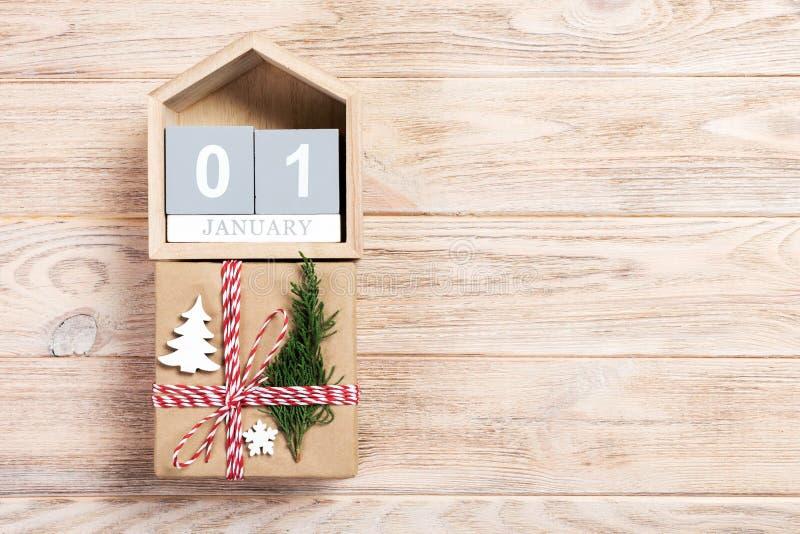 Kalender mit Datum am 1. Januar und Geschenkboxen auf Farbhintergrund Weihnachtsniederlassung und -glocken stockfotografie