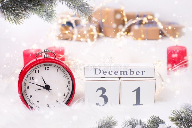 Kalender och r?d klocka - symbol av det nya ?ret, felika ljus och birning stearinljus p? vit p?lsbakgrund royaltyfri foto