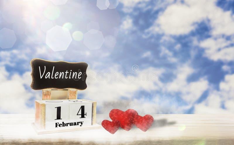 Kalenderask med svart tavla för skrivande in text, Februari 14, förälskelsedag, rött hjärtaställe på trätabellen, ljus bakgrund f royaltyfria foton