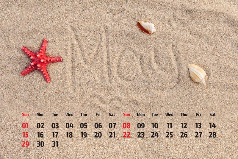 Kalendern med sjöstjärnan och snäckskal på sand sätter på land Maj 2016 royaltyfri bild