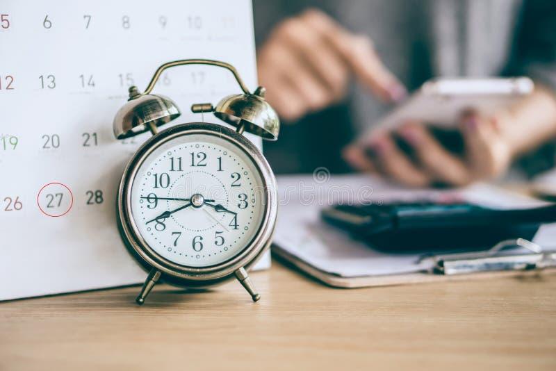 Kalendern och ringklockan för förfallet datum med suddighetsaffärskvinnan räcker beräkning royaltyfri fotografi