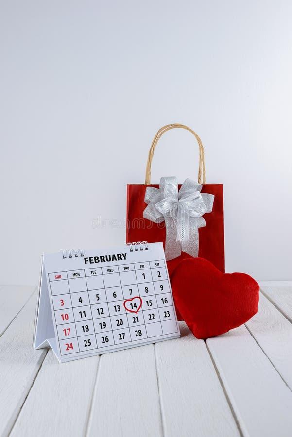 Kalendersida med en skriftlig hjärtaviktig för röd hand på Februari 14 av den Sanka valentindagen arkivbild