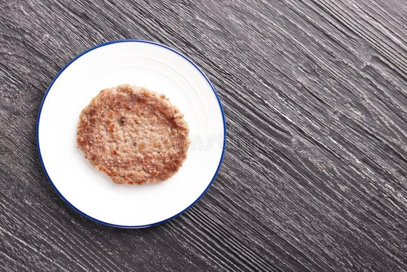 Kalfsvleeskotelet op een witte plaat met een blauwe ring stock foto's