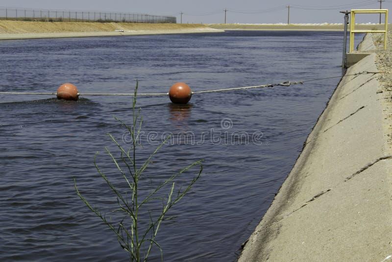 Kalifornien-Aquädukt: blaue Wasserströme hinter einer Linie von roten Bällen stockfotos