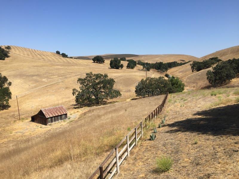 Kalifornien landskap med ett staket och lite en röd ladugård arkivfoto